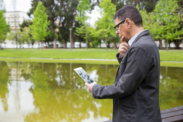Uomo pensieroso che utilizza compressa e in piedi nel parco della città