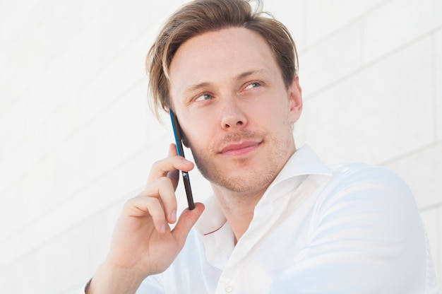 Uomo pensieroso di affari che rivolge allo smartphone all'aperto
