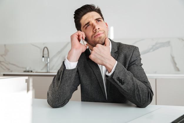 Uomo pensieroso di affari che si siede dalla tavola a casa