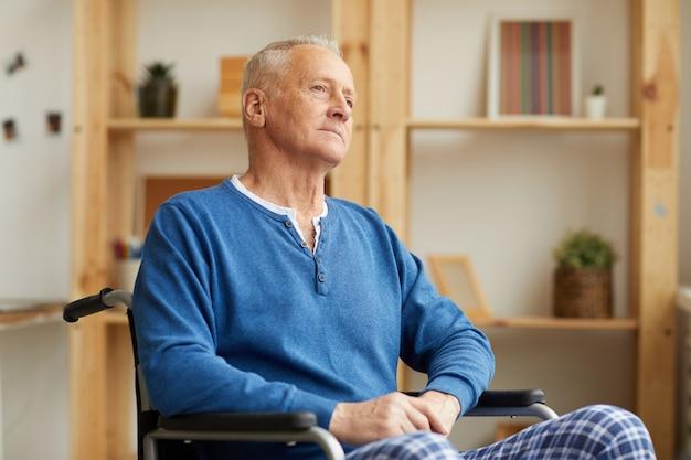 Uomo pensieroso in sedia a rotelle
