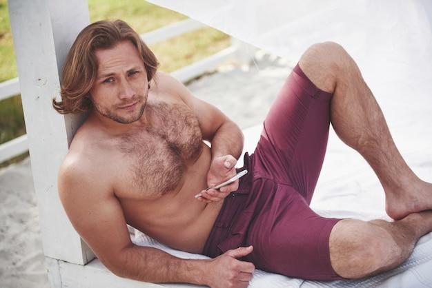 Uomo perfetto sexy alla moda sulla spiaggia.