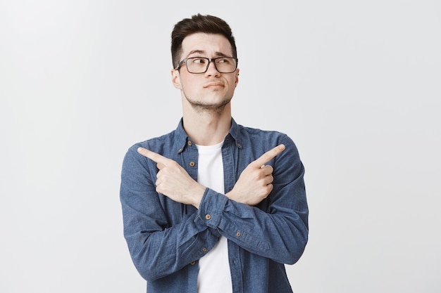 Uomo perplesso con gli occhiali che prende una decisione, puntando le dita lateralmente