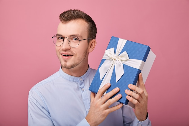 Uomo piacevolmente sorpreso in camicia delicatamente blu con gli occhiali guarda la cornice con sorpresa
