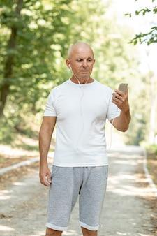 Uomo più anziano del colpo medio cheking il suo telefono