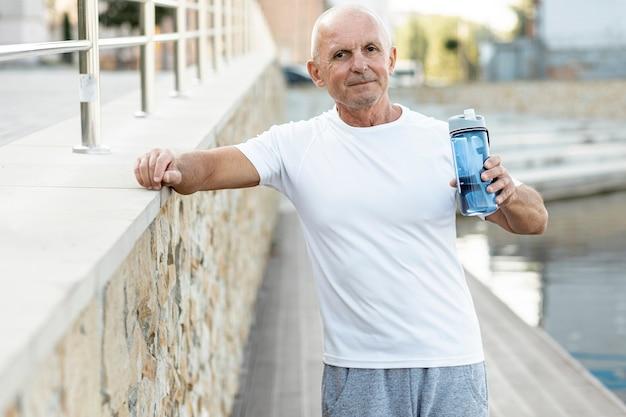 Uomo più anziano sorridente che guarda nel riposo della macchina fotografica