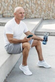 Uomo più anziano sorridente che riposa tenendo il suo telefono