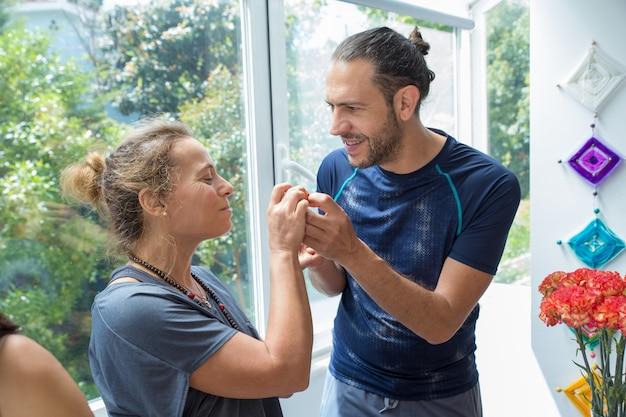 Uomo positivo e donna che chiacchierano nella cucina