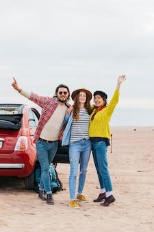 Uomo positivo e donne allegre che abbracciano vicino auto sulla costa del mare