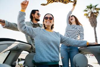 Uomo positivo e donne sorridenti divertendosi e sporgendosi dall'automobile