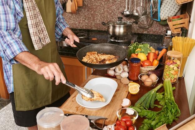Uomo potato in grembiule che mette pollo fritto dalla padella al piatto