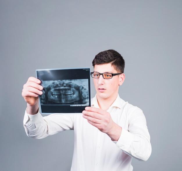 Uomo premuroso che esamina i raggi x dei denti