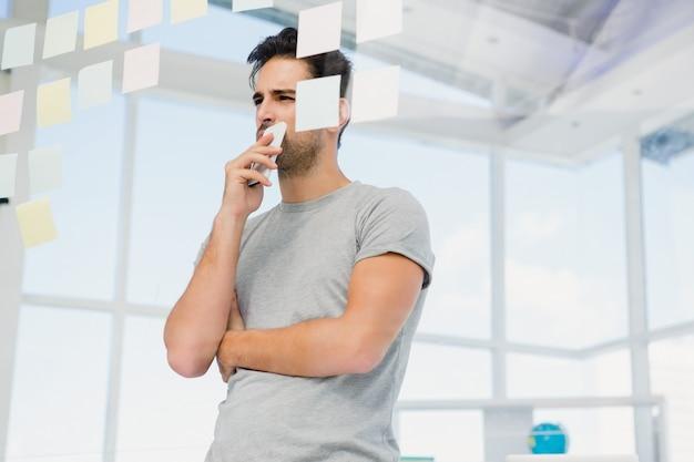 Uomo premuroso che esamina le note appiccicose sulla finestra