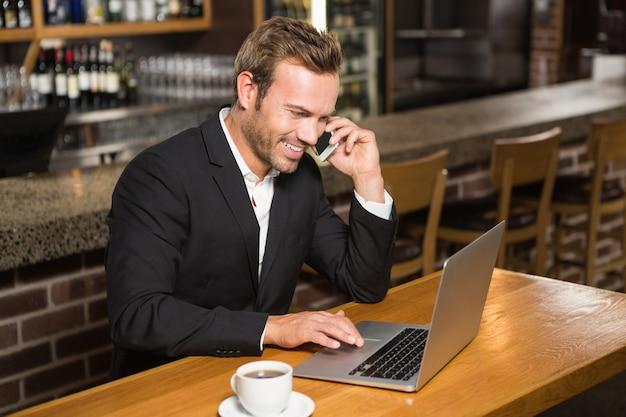 Uomo premuroso che per mezzo del computer portatile e avendo una telefonata