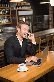 Uomo premuroso che per mezzo del computer portatile e dello smartphone