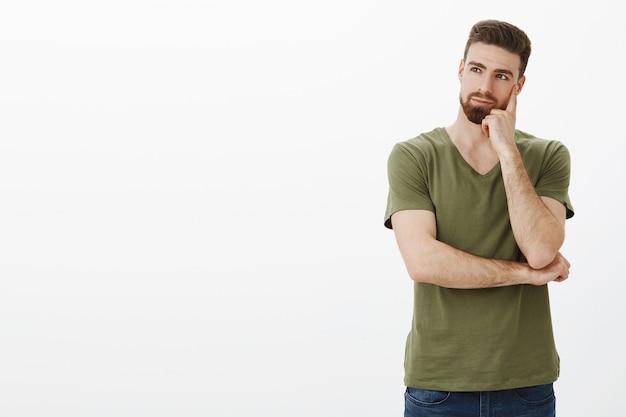 Uomo premuroso che tiene il pugno sulla guancia guardando a sinistra copyspace