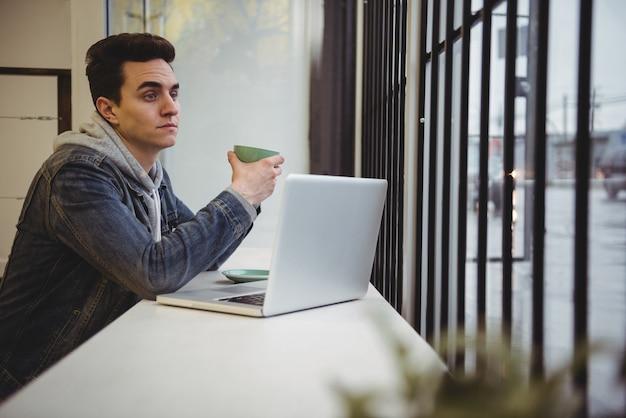 Uomo premuroso che tiene tazza di caffè
