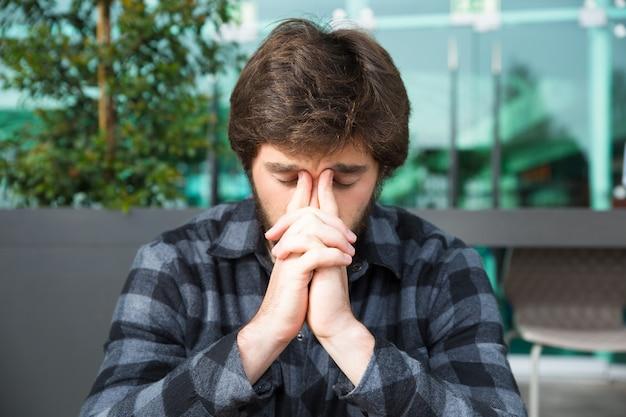 Uomo premuroso che tocca il ponte del naso e che pensa in caffè della via