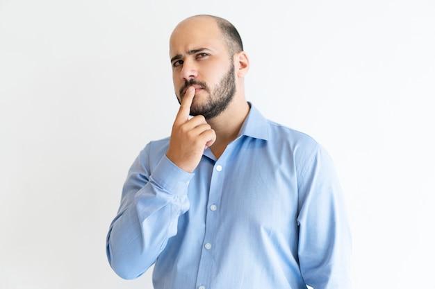 Uomo premuroso che tocca la bocca con il dito e guardando lontano