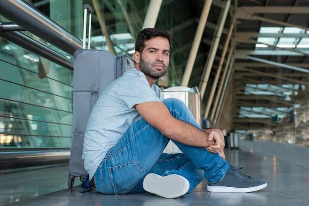 Uomo premuroso stanco che si siede sul pavimento all'aeroporto