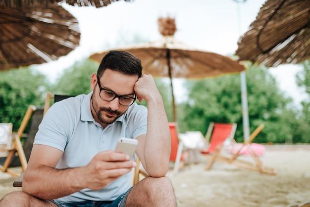 Uomo preoccupato che per mezzo del telefono mentre sedendosi su una spiaggia.
