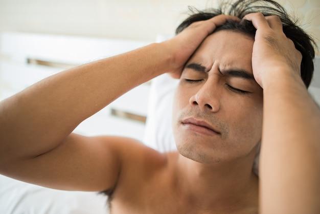Uomo preoccupato che si siede sul letto la mattina, pensando seria qualcosa
