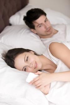 Uomo preoccupato che sospetta la sua fidanzata che tradisce usando il cellulare i