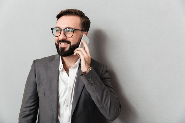 Uomo professionale bello nell'usura convenzionale che ha conversazione mobile facendo uso dello smartphone isolato sopra grey