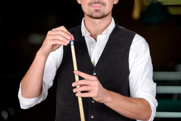 Uomo professionale che gioca a biliardo nel club di biliardo scuro