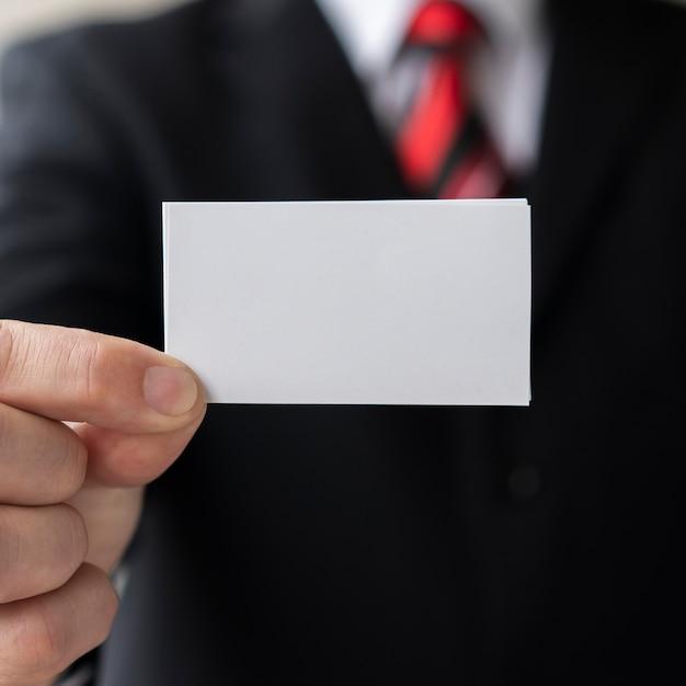 Uomo professionale che tiene biglietto da visita in bianco