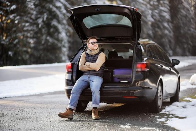 Uomo pronto ad andare in vacanza e rilassarsi nel bagagliaio aperto di una macchina prima di un viaggio