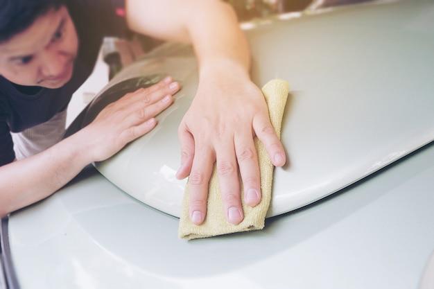 Uomo pulito e cerare l'auto - concetto di servizio di manutenzione auto all'aperto