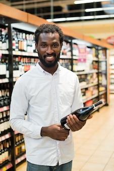 Uomo raccolta bottiglia di vino nella sezione alcolica
