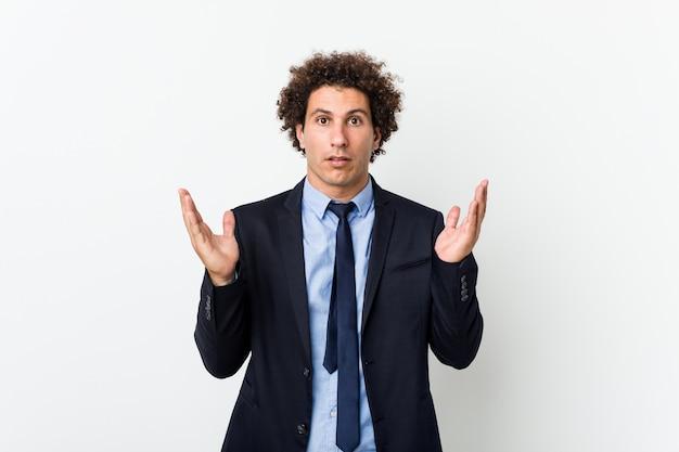 Uomo riccio di giovani affari contro fondo bianco sorpreso e colpito.