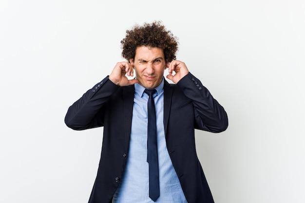 Uomo riccio di giovani affari contro le orecchie bianche del rivestimento murale con le mani.