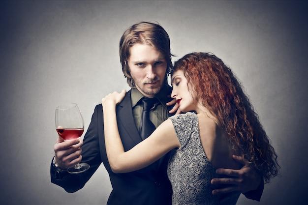 Uomo ricco che tiene un bicchiere di vino e una donna
