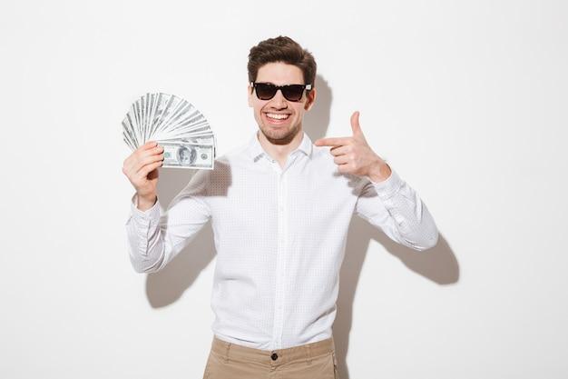 Uomo ricco e felice in camicia e occhiali da sole, rallegrandosi e puntando il dito su un sacco di soldi denaro contante, isolato su muro bianco con ombra