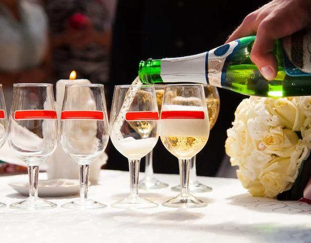 Uomo riempire bicchieri di champagne sulla festa di nozze