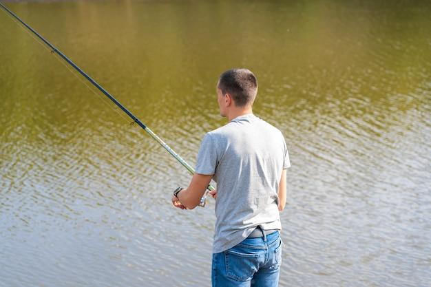 Uomo rilassante e pesca in riva al lago