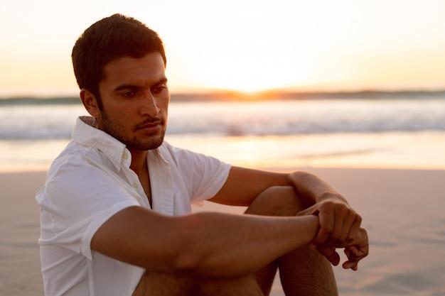 Uomo rilassante sulla spiaggia