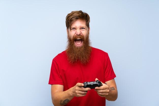 Uomo rossa con la barba lunga, giocando con un controller di videogioco
