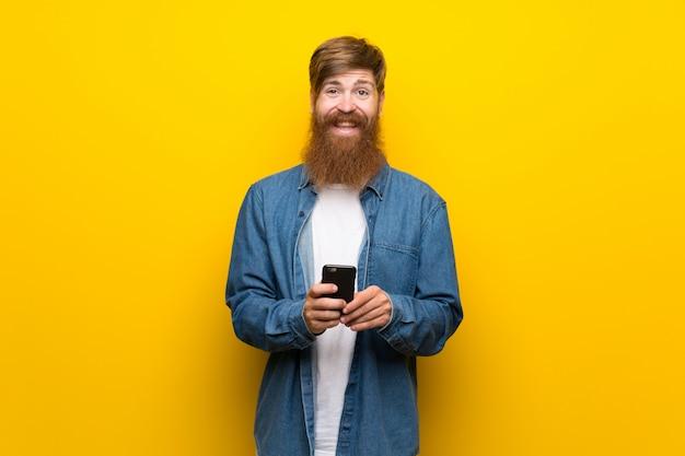 Uomo rossa con la barba lunga sul muro giallo con il cellulare
