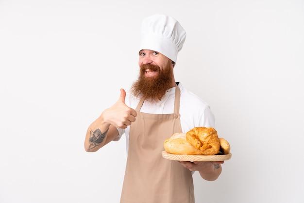 Uomo rossa in uniforme da chef. panettiere maschio che tiene un tavolo con diversi pani con il pollice in alto perché è successo qualcosa di buono
