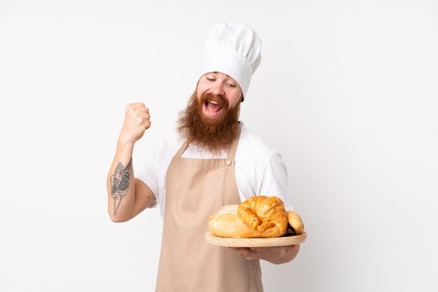 Uomo rossa in uniforme da chef. panettiere maschio che tiene una tabella con parecchi pani che celebra una vittoria