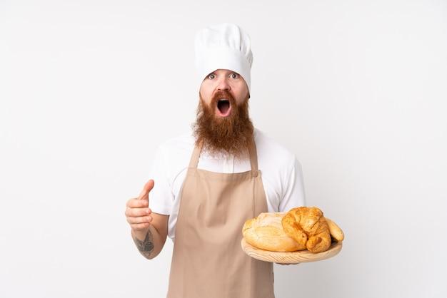 Uomo rossa in uniforme da chef. panettiere maschio che tiene una tabella con parecchi pani con l'espressione facciale sorpresa e colpita
