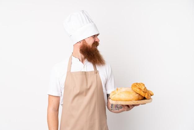 Uomo rossa in uniforme da chef. panettiere maschio che tiene una tavola con parecchi pani con l'espressione felice
