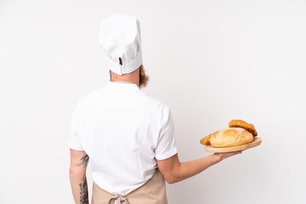 Uomo rossa in uniforme da chef. panettiere maschio che tiene una tavola con parecchi pani nella posizione posteriore