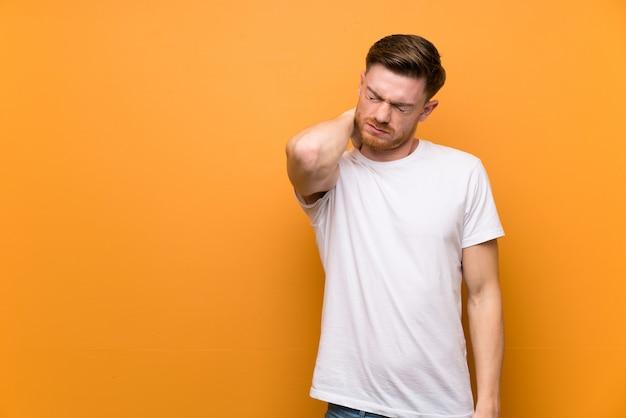 Uomo rossa sul muro marrone con mal di collo