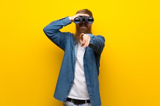 Uomo rosso con la barba lunga sul muro giallo con binocolo nero
