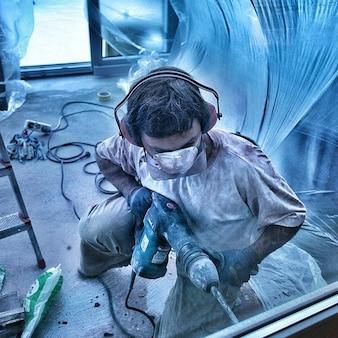 Uomo rovina martello trapano attrezzature demolizione