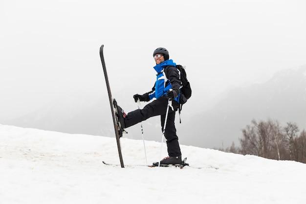 Uomo sciatore in cima alla montagna. nebbia. stagione invernale